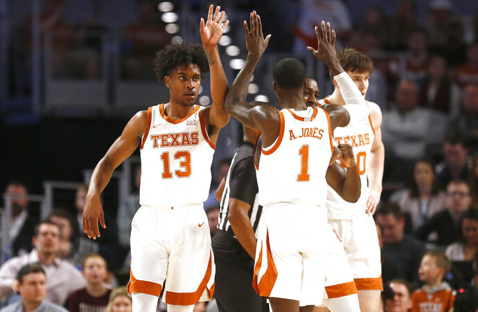 Texas guard Jase Febres (13) celebrates with teammate guard Andrew Jones (1) as Texas plays Texas A&M during the first half of an NCAA college basketball game, Sunday, Dec. 8, 2019, in Fort Worth, Texas. Texas won 60-50. (AP Photo/Ron Jenkins)