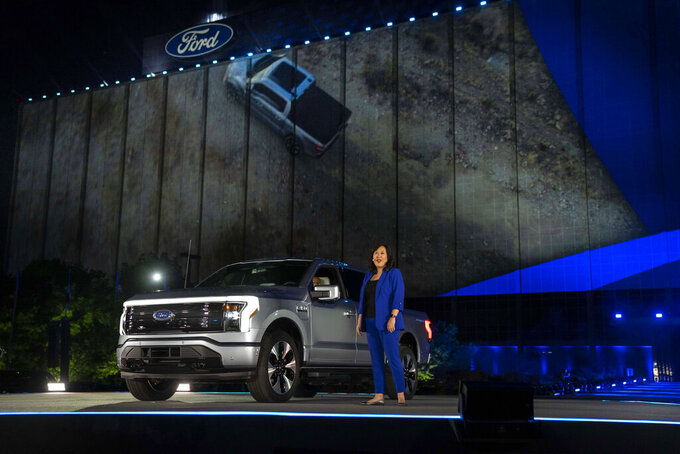 In a photo provided by Ford, Linda Zhang, F-150 Lightning chief engineer, explains details of Ford's first all-electric truck at the reveal of the vehicle at Ford headquarters in Dearborn, Mich., Wednesday, May 19, 2021. the pickup will be able to travel up to 300 miles per battery charge, thanks to a frame designed to safely hold a huge lithium-ion battery that can power your house should the electricity go out. Going from zero to 60 mph (97 kilometers per hour) will take just 4.5 seconds. (Eric Perry/Ford via AP)