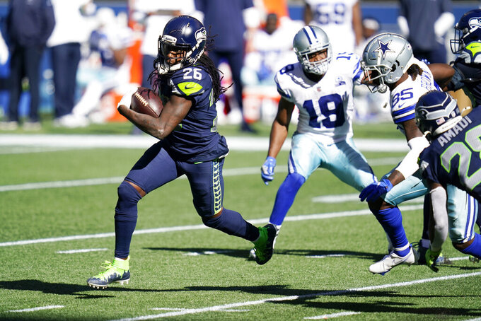 Seattle Seahawks cornerback Shaquill Griffin (26) runs with the ball after intercepting a pass against the Dallas Cowboys during the first half of an NFL football game, Sunday, Sept. 27, 2020, in Seattle. (AP Photo/Elaine Thompson)