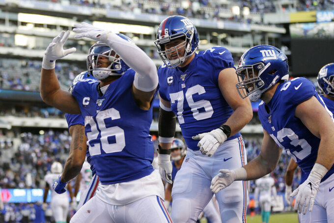 New York Giants running back Saquon Barkley (26) celebrates with teammates after scoring a touchdown in the second half of an NFL football game against the Miami Dolphins, Sunday, Dec. 15, 2019, in East Rutherford, N.J. (AP Photo/Adam Hunger)