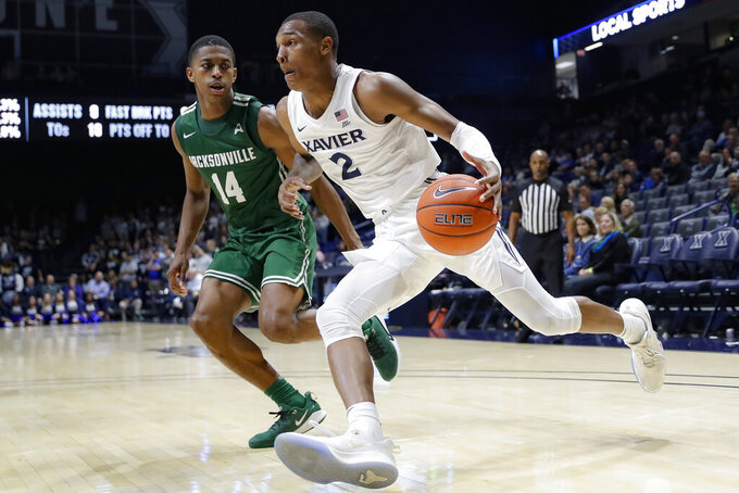 Xavier's Dahmir Bishop (2) drives against Jacksonville's Mo Arnold (14) during the second half of an NCAA college basketball game Tuesday, Nov. 5, 2019, in Cincinnati. (AP Photo/John Minchillo)