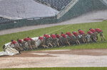 Grounds crew members unroll the tarp to cover the baseball diamond from a heavy downpour delaying the baseball game during the sixth inning of a baseball game between the Washington Nationals and the Baltimore Orioles in Washington, Sunday, Aug. 9, 2020. (AP Photo/Manuel Balce Ceneta)