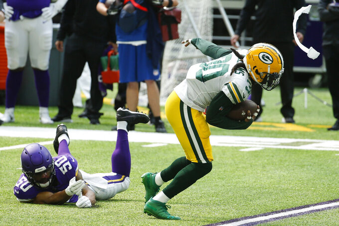 Green Bay Packers running back Jamaal Williams runs from Minnesota Vikings linebacker Eric Wilson, left, during the first half of an NFL football game, Sunday, Sept. 13, 2020, in Minneapolis. (AP Photo/Bruce Kluckhohn)
