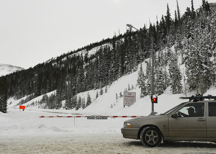 In a March 8, 2019 photo, a driver turns around at a road closed sign along US 6 on Loveland Pass in Dillon, Colorado. A 29-year-old Fort Collins woman died Sunday, Dec. 8, 2019 in an avalanche while backcountry skiing in northern Colorado. It's the first avalanche death this winter season in Colorado, according to the Colorado Avalanche Information Center.  (RJ Sangosti/The Denver Post via AP)
