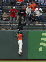 San Francisco Giants left fielder Mac Williamson jumps as fans reach for a solo home run by Arizona Diamondbacks' Ildemaro Vargas during the first inning of a baseball game in San Francisco, Friday, May 24, 2019. (AP Photo/Jeff Chiu)