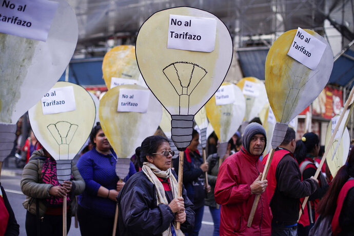 People hold cutouts that look like light bulbs with signs that read in Spanish