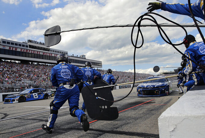 Chase Elliott's crew dashes into the lane to service his car during a pit stop in the NASCAR Cup Series auto race at New Hampshire Motor Speedway in Loudon, N.H., Sunday, July 21, 2019. (AP Photo/Charles Krupa)