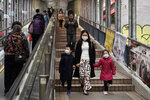 People wearing masks, walk on street in Central, a business district in Hong Kong, Wednesday, Feb. 19, 2020. Russia says it will temporarily ban Chinese nationals from entering the country amid the outbreak of the new virus centered in China that has infected more than 73,000 people. (AP Photo/Kin Cheung)