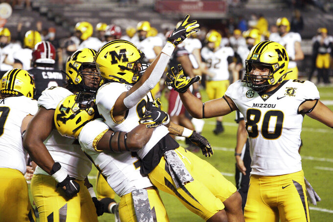 Missouri wide receiver Tauskie Dove, center, Javon Foster, left, Larry Rountree III, second from left, and Messiah Swinson (80) celebrate Dove's touchdown reception during the first half of an NCAA college football game against South Carolina, Saturday, Nov. 21, 2020, in Columbia, S.C. (AP Photo/Sean Rayford)