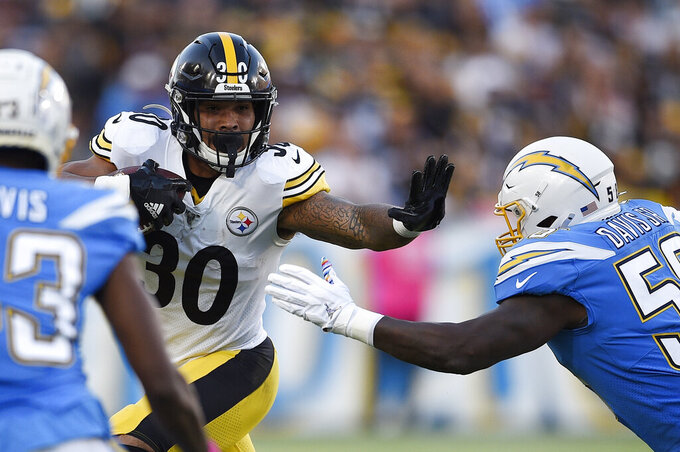 Pittsburgh Steelers running back James Conner, left, holds by Los Angeles Chargers outside linebacker Thomas Davis as he runs the ball during the first half of an NFL football game, Sunday, Oct. 13, 2019, in Carson, Calif. (AP Photo/Kelvin Kuo)