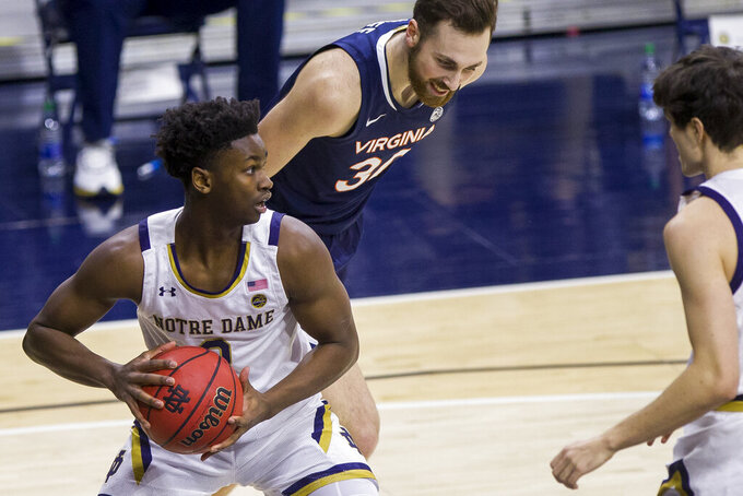 Notre Dame's Trey Wertz (2) looks downcourt after grabbing a rebound in front of Virginia's Jay Huff (30) during the first half of an NCAA college basketball game Wednesday, Dec. 30, 2020, in South Bend, Ind. (AP Photo/Robert Franklin)
