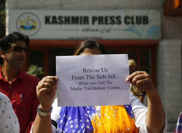 FILE- In this Oct. 3, 2019 file photo, Kashmiri journalists displays a placard during a protest against the communication blackout in Srinagar, Indian controlled Kashmir. Journalists in disputed Kashmir urged the Indian government on Monday to allow them to report freely and expressed concern about alleged police harassment since the region's semi-autonomy was rescinded in August amid an unprecedented lockdown. (AP Photo/Mukhtar Khan, File)
