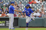 Toronto Blue Jays' Freddy Galvis, right, is greeted by third base coach Luis Rivera after hitting a solo home run off Baltimore Orioles starting pitcher Dylan Bundy during the third inning of a baseball game, Saturday, Aug. 3, 2019, in Baltimore. (AP Photo/Julio Cortez)