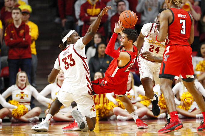 Texas Tech guard Davide Moretti passes around Iowa State forward Solomon Young (33) during the first half of an NCAA college basketball game Saturday, Feb. 22, 2020, in Ames, Iowa. (AP Photo/Charlie Neibergall)