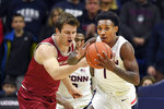 Connecticut's Christian Vital (1) steals the ball from Saint Joseph's guard Ryan Daly (1) in the first half of an NCAA college basketball game Wednesday, Nov. 13, 2019, in Storrs, Conn. (AP Photo/Stephen Dunn)