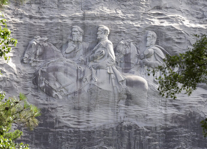 """FILE - This June 23, 2015, file photo shows a carving depicting Confederates Stonewall Jackson, Robert E. Lee and Jefferson Davis in Stone Mountain, Ga. A coalition of civil rights groups in Atlanta is using this year's Super Bowl to kick off a renewed """"war on the Confederacy,"""" in a fight to remove Confederate monuments around the nation (AP Photo/John Bazemore, File)"""