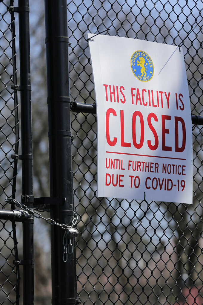 A sign is displayed on locked tennis courts in Branch Brook Park in Newark, N.J., Thursday, March 26, 2020. New Jersey's death toll from the coronavirus has nearly doubled in the past two days, Gov. Phil Murphy said Thursday. President Donald Trump signed a declaration naming New Jersey a disaster area eligible for additional funding. (AP Photo/Seth Wenig)
