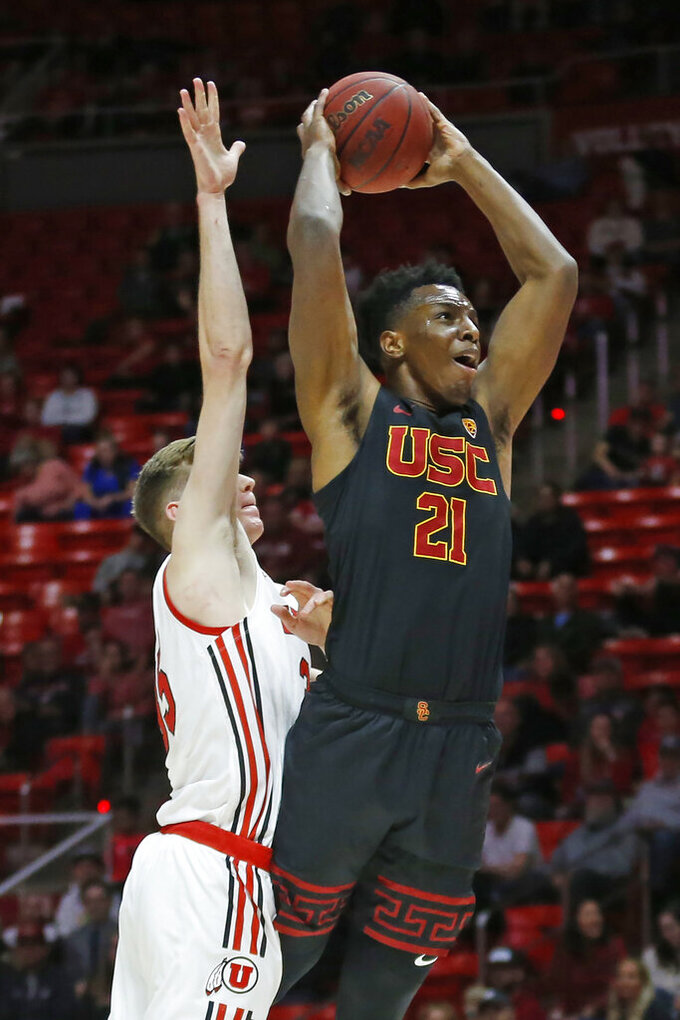 Utah center Branden Carlson, left, defends as USC forward Onyeka Okongwu (21) goes to the basket in the first half of an NCAA college basketball game Sunday, Feb. 23, 2020, in Salt Lake City. (AP Photo/Rick Bowmer)