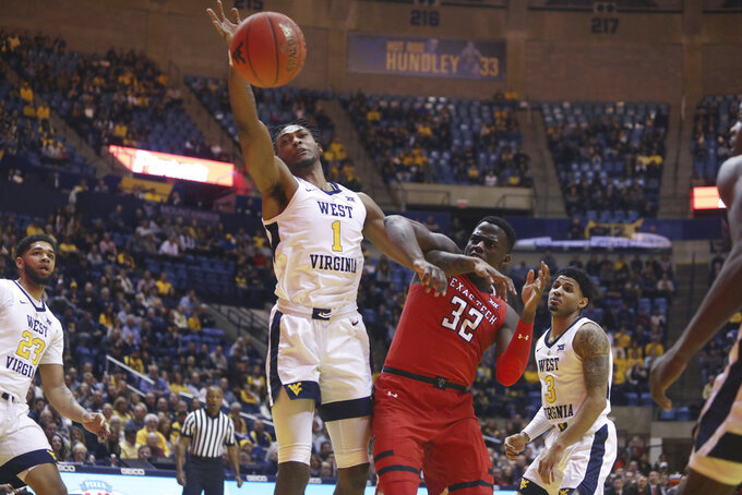 West Virginia forward Derek Culver (1) rebounds the ball while defended by Texas Tech center Norense Odiase (32) during the first half of an NCAA college basketball game Wednesday, Jan. 2, 2019, in Morgantown, W.Va. (AP Photo/Raymond Thompson)