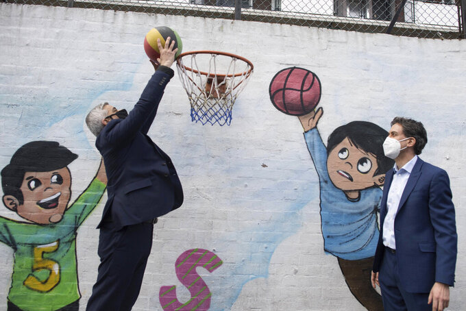 Mayor of London Sadiq Khan, left, jumps for the basket, joined by Labour Party shadow business secretary Ed Miliband at the Play, Adventure & Community Engagement Fairfield Play Centre in London, Tuesday April 6, 2021.  Khan and Miliband met with staff and children as they take part in hands-on, environmentally-friendly activities following launching Khan's election manifesto ahead of the London Mayoral election. (Stefan Rousseau/PA via AP)