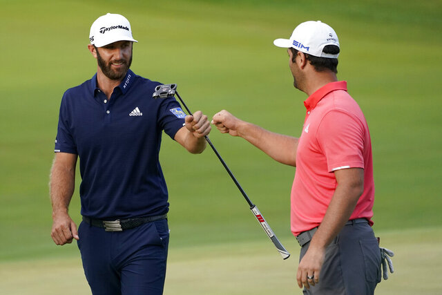 Jon Rahm, right, is congratulated by Dustin Johnson on the first playoff hole during the final round of the BMW Championship golf tournament at the Olympia Fields Country Club in Olympia Fields, Ill., Sunday, Aug. 30, 2020. (AP Photo/Charles Rex Arbogast)