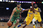 Boston Celtics forward Jayson Tatum (0) drives to the basket against Los Angeles Lakers guard Rajon Rondo (9) and forward LeBron James (23) during the first half of an NBA basketball game in Boston, Monday, Jan. 20, 2020. (AP Photo/Charles Krupa)