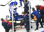 Toronto Maple Leafs defenseman Jake Muzzin (8) leaves the ice on a stretcher as teammate Maple Leafs right wing Mitchell Marner (16) pats him on the pants while playing against the Columbus Blue Jackets during the third period of an NHL hockey playoff game  Tuesday, Aug. 4, 2020 in Toronto. (Nathan Denette/The Canadian Press via AP)
