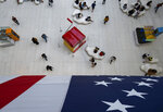 People walk under a flag in the Oculus transportation hub Wednesday, Sept. 11, 2019, in New York. From Europe to Japan, President Donald Trump has stirred up under-the-radar trade disputes that potentially could erupt within weeks or months with damaging consequences.  (AP Photo/Craig Ruttle)