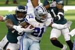 Philadelphia Eagles defensive end Vinny Curry (75) reaches out to stop Dallas Cowboys running back Ezekiel Elliott (21) in the first half of an NFL football game in Arlington, Texas, Sunday, Dec. 27. 2020. (AP Photo/Ron Jenkins)