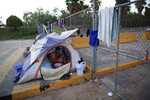 Honduran migrant Jose Antonio Sanchez Escalante, 24, who has been camping out for two months as he waits his turn to request asylum in the U.S., begins his day at the entrance to the Puerta Mexico bridge, in Matamoros, Mexico, Thursday, June 27, 2019. Hundreds of migrants from Central America, South America, the Caribbean and Africa have been waiting for their number to be called at the bridge in downtown Matamoros, to have the opportunity to request asylum. With the exception of a handful of migrants who had been there for months, authorities have prohibited camping and migrants have had to move to rented rooms and one distant private shelter.(AP Photo/Rebecca Blackwell)