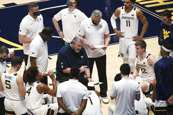West Virginia coach Bob Huggins, center, speaks with players during the second half of an NCAA college basketball game against Oklahoma, Saturday, Feb. 13, 2021, in Morgantown, W.Va. (AP Photo/Kathleen Batten)
