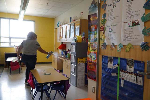 Fort Worth ISD employee Yolanda Cintron assists with a deep cleaning at the Leadership Academy at John T. White Elementary School in Fort Worth, Texas on Thursday, March 12, 2020. (Lawrence Jenkins/The Dallas Morning News via AP)