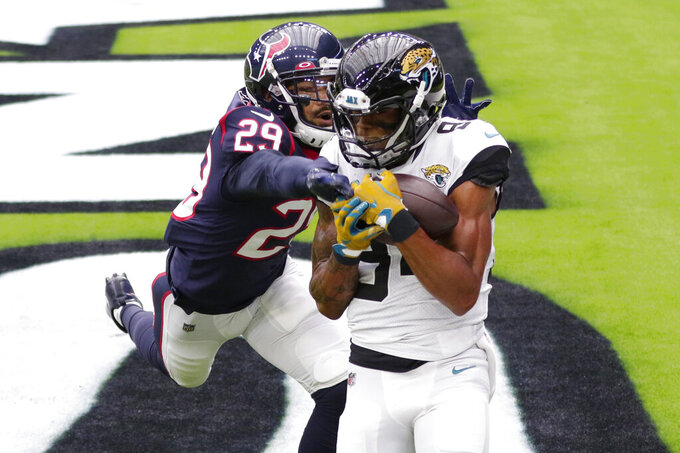 Jacksonville Jaguars wide receiver Keelan Cole (84) catches a pass over Houston Texans cornerback Phillip Gaines (29) for a touchdown during the first half of an NFL football game Sunday, Oct. 11, 2020, in Houston. (AP Photo/Michael Wyke)
