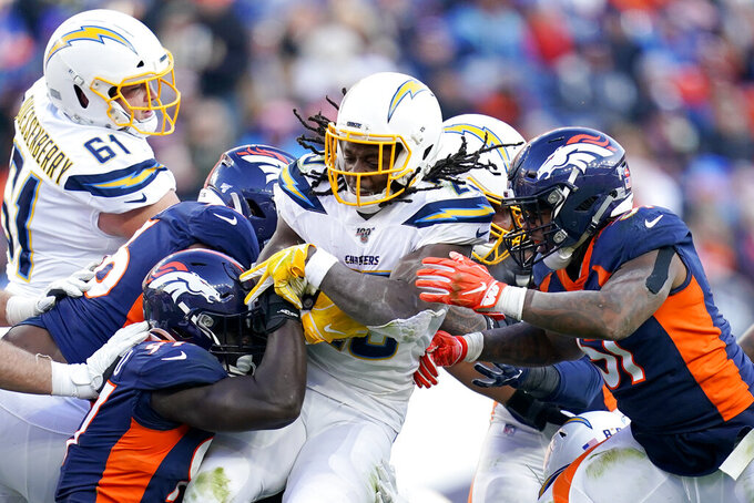 Los Angeles Chargers running back Melvin Gordon is tackled by the against the Denver Broncos during the first half of an NFL football game Sunday, Dec. 1, 2019, in Denver. (AP Photo/Jack Dempsey)
