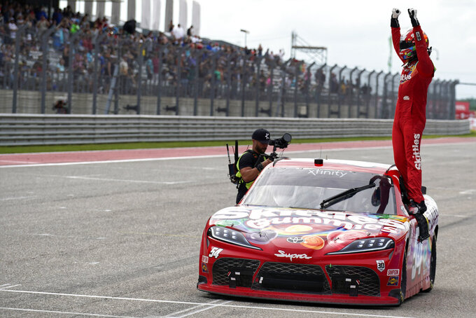 Kyle Busch stands on his car as he celebrates after winning the NASCAR Xfinity Series auto race at the Circuit of the Americas in Austin, Texas, Saturday, May 22, 2021. (AP Photo/Chuck Burton)
