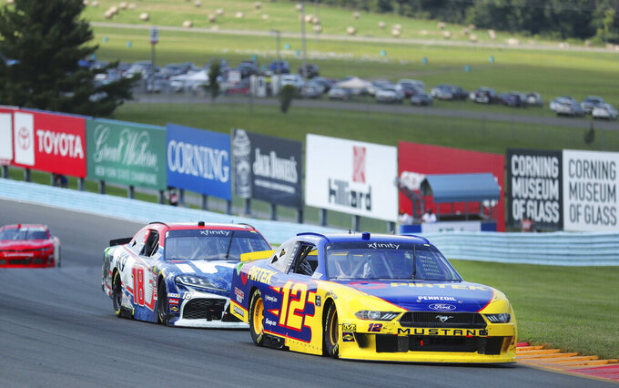 Kyle Busch (18) closely pursues Ryan Blaney (12) just before spinning out in a NASCAR Xfinity Series auto race at Watkins Glen International, Saturday, Aug. 3, 2019, in Watkins Glen, N.Y. (AP Photo/John Munson)
