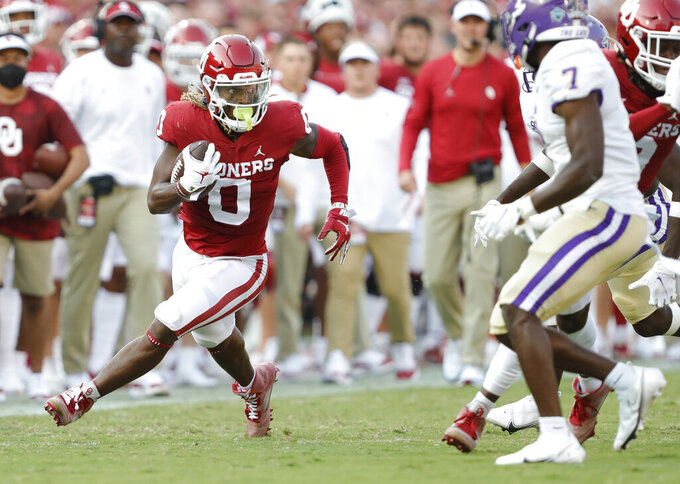 Oklahoma running back Eric Gray (0) looks at Western Carolina safety Charles Gadie (7) on a run during the first half of an NCAA college football game Saturday, Sept. 11, 2021, in Norman, Okla. (AP Photo/Alonzo Adams)