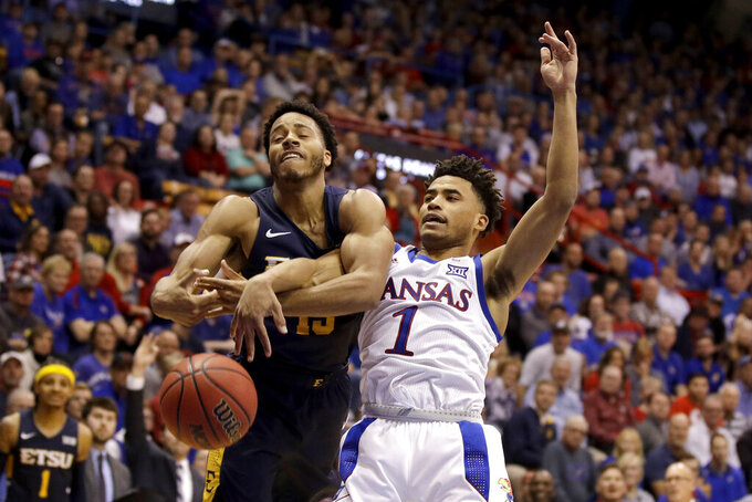 East Tennessee State guard Isaiah Tisdale, left, and Kansas guard Devon Dotson (1) battle for a rebound during the second half of an NCAA college basketball game Tuesday, Nov. 19, 2019, in Lawrence, Kan. Kansas won 75-63. (AP Photo/Charlie Riedel)