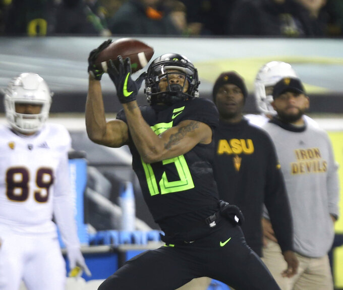 Oregon's Dillon Mitchell, center, catches a Justin Herbert pass in front of the Arizona State bench on his way to a second quarter touchdown in an NCAA college football game Saturday, Nov. 17, 2018, in Eugene, Ore. (AP Photo/Chris Pietsch)