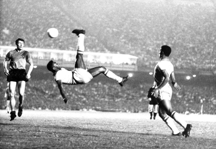FILE - In this Sept. 1968 file photo, Brazil's Pele kicks the ball during a friendly soccer game against Belgium in Rio de Janeiro, Brazil. On Oct. 23, 2020, the three-time World Cup winner Pelé turns 80 without a proper celebration amid the COVID-19 pandemic as he quarantines in his mansion in the beachfront city of Guarujá, where he has lived since the start of the pandemic.  (AP Photo, File)