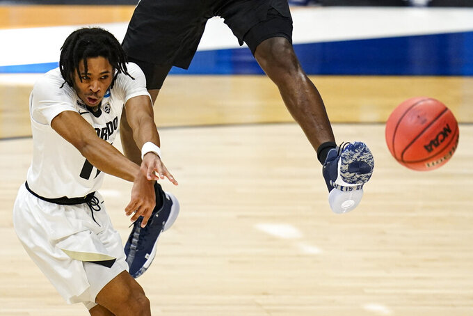 Colorado guard Keeshawn Barthelemy (11) makes a pass over the foot of Georgetown center Qudus Wahab (34) in the first half of a first-round game in the NCAA men's college basketball tournament at Hinkle Fieldhouse in Indianapolis, Saturday, March 20, 2021. (AP Photo/Michael Conroy)