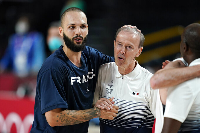France's Evan Fournier (10) celebrates with head coach Vincent Collet at the end of a men's basketball semifinal round game against Slovenia at the 2020 Summer Olympics, Thursday, Aug. 5, 2021, in Saitama, Japan. (AP Photo/Charlie Neibergall)