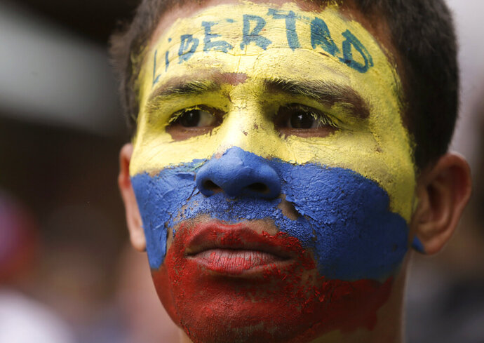 An opponent to Venezuela's President Nicolas Maduro, his face painted the colors of the Venezuelan national flag and with the Spanish word for