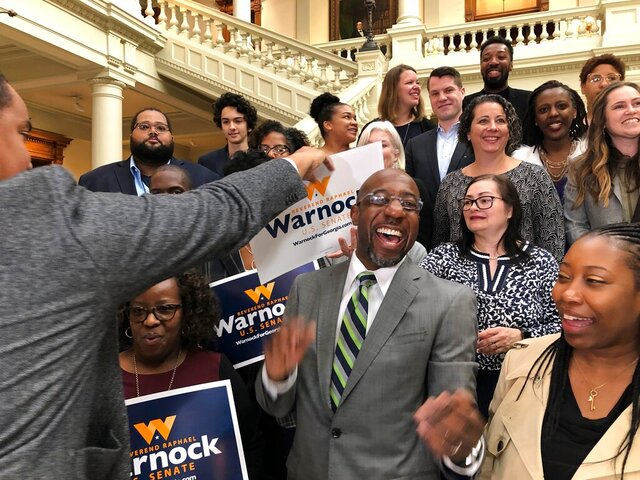 The Rev. Raphael Warnock, a Georgia Democrat, greets supporters at the state Capitol in Atlanta on Friday, March 6, 2020. Warnock filed paperwork to appear on the Nov. 3 ballot for Georgia's special U.S. Senate election. (AP Photo/Benjamin Nadler)