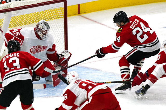 Chicago Blackhawks center Pius Suter, right, scores his second goal against Detroit Red Wings goalie Jonathan Bernier during the first period of an NHL hockey game in Chicago, Sunday, Jan. 24, 2021. (AP Photo/Nam Y. Huh)