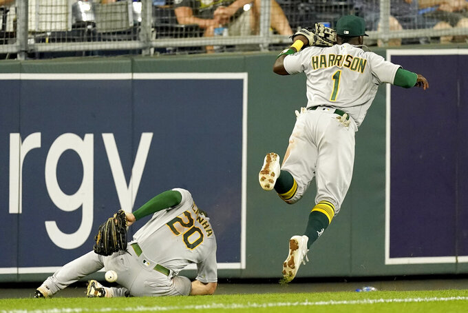 Oakland Athletics third baseman Josh Harrison (1) and left fielder Mark Canha (20) can't catch a fly foul ball hit by Kansas City Royals' Whit Merrifield during the fifth inning of a baseball game Wednesday, Sept. 15, 2021, in Kansas City, Mo. (AP Photo/Charlie Riedel)