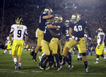FILE - In this Sept. 22, 2012, file photo, Notre Dame's Nicky Baratti, second from right, is congratulated by teammates after intercepting a pass intended for Michigan's Drew Dileo (9) during the first half of an NCAA college football game, in South Bend, Ind. The NCAA has denied Notre Dame's appeal of a decision to vacate 21 victories because of academic misconduct, including all 12 wins from the school's 2012 national championship game run. (AP Photo/Darron Cummings, File)
