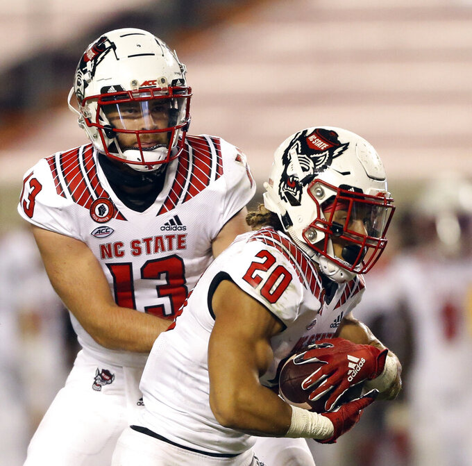 North Carolina State quarterback Devin Leary (13) hands off to running back Jordan Houston (20) for a touchdown run in the second half of an NCAA college football game against Virginia Tech, Saturday, Sept. 26, 2020, in Blacksburg, Va. (Matt Gentry/The Roanoke Times via AP, Pool)