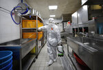 A health official wearing protective gear sprays disinfectant to help reduce the spread the new coronavirus ahead of school reopening in a cafeteria at a high school in Seoul, South Korea, Monday, May 11, 2020. (AP Photo/Lee Jin-man)