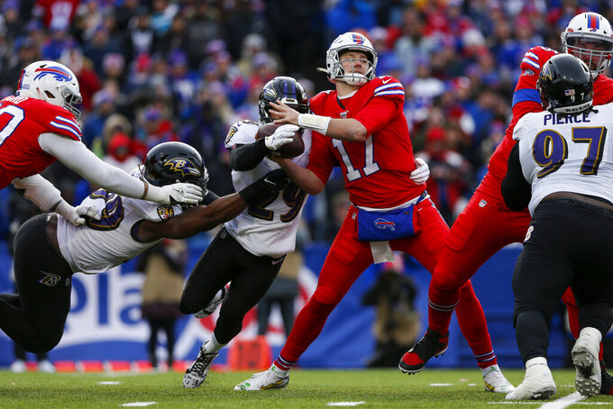 Buffalo Bills quarterback Josh Allen (17) has the ball stripped by Baltimore Ravens free safety Earl Thomas (29) and Matt Judon (99) during the second half of an NFL football game in Orchard Park, N.Y., Sunday, Dec. 8, 2019. The Bills recovered the fumble. (AP Photo/John Munson)